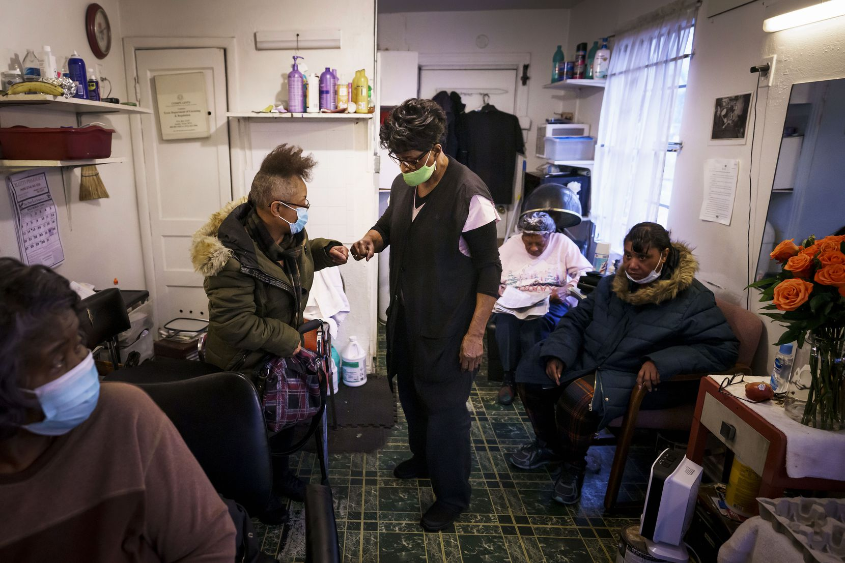 """Earnestine Tarrant fist bumps with Sharon Curtis at her hair salon in South Dallas on her final day working before her retirement, Thursday, Dec. 31, 2020.  """"I can't hug you, so we have to fist bump,"""" Tarrant said with a laugh."""