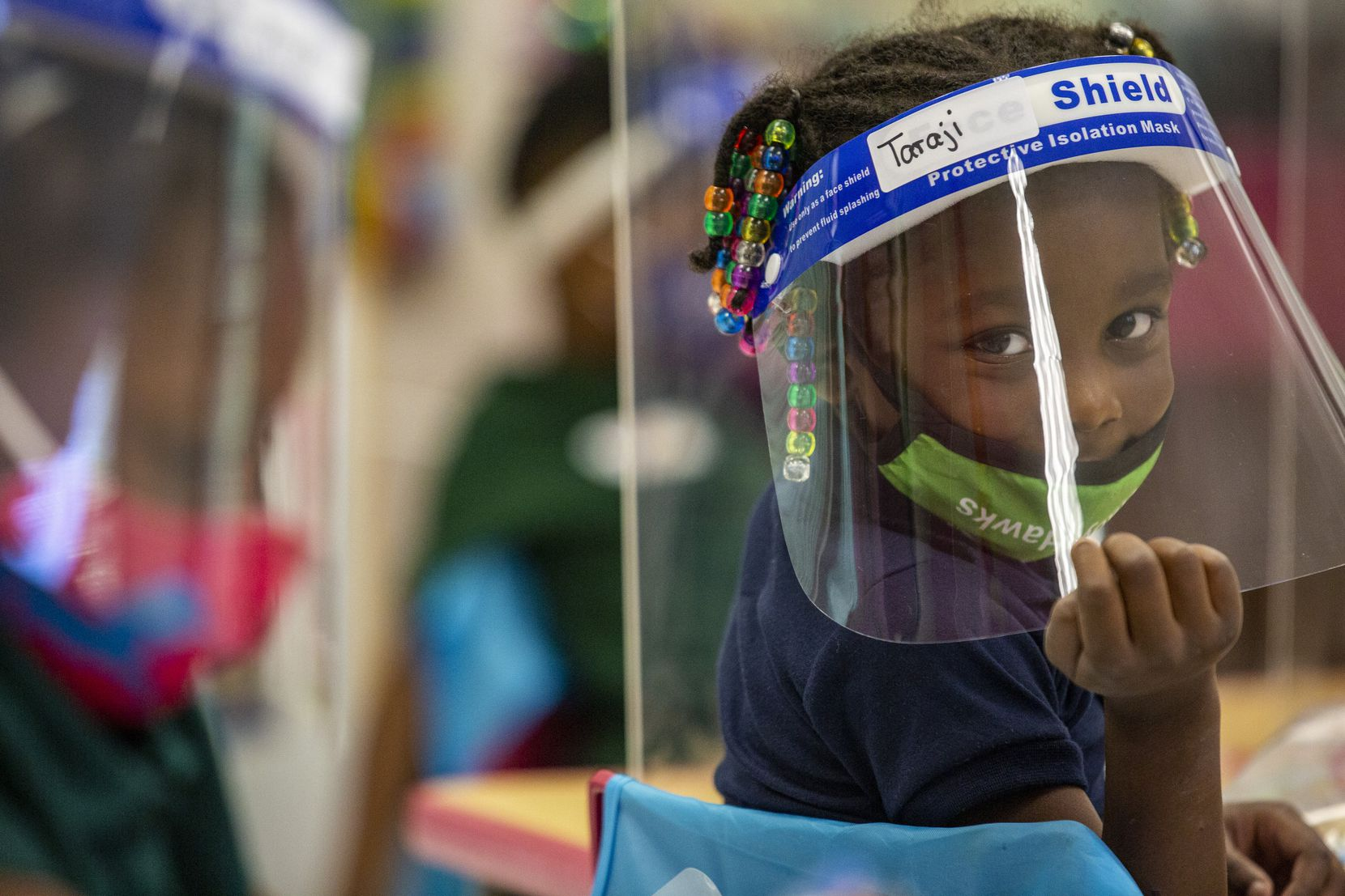 Pre-K 4 student Taraji Thomas poses for a portrait while working on an activity behind a sneeze guard installed on her desk alongside her classmates at N.W. Harllee Early Childhood Center in the Oak Cliff neighborhood of Dallas on Friday, Oct. 2, 2020. Dallas ISD's Pre-K numbers are down by the thousands to start the school year. (Lynda M. González/The Dallas Morning News)
