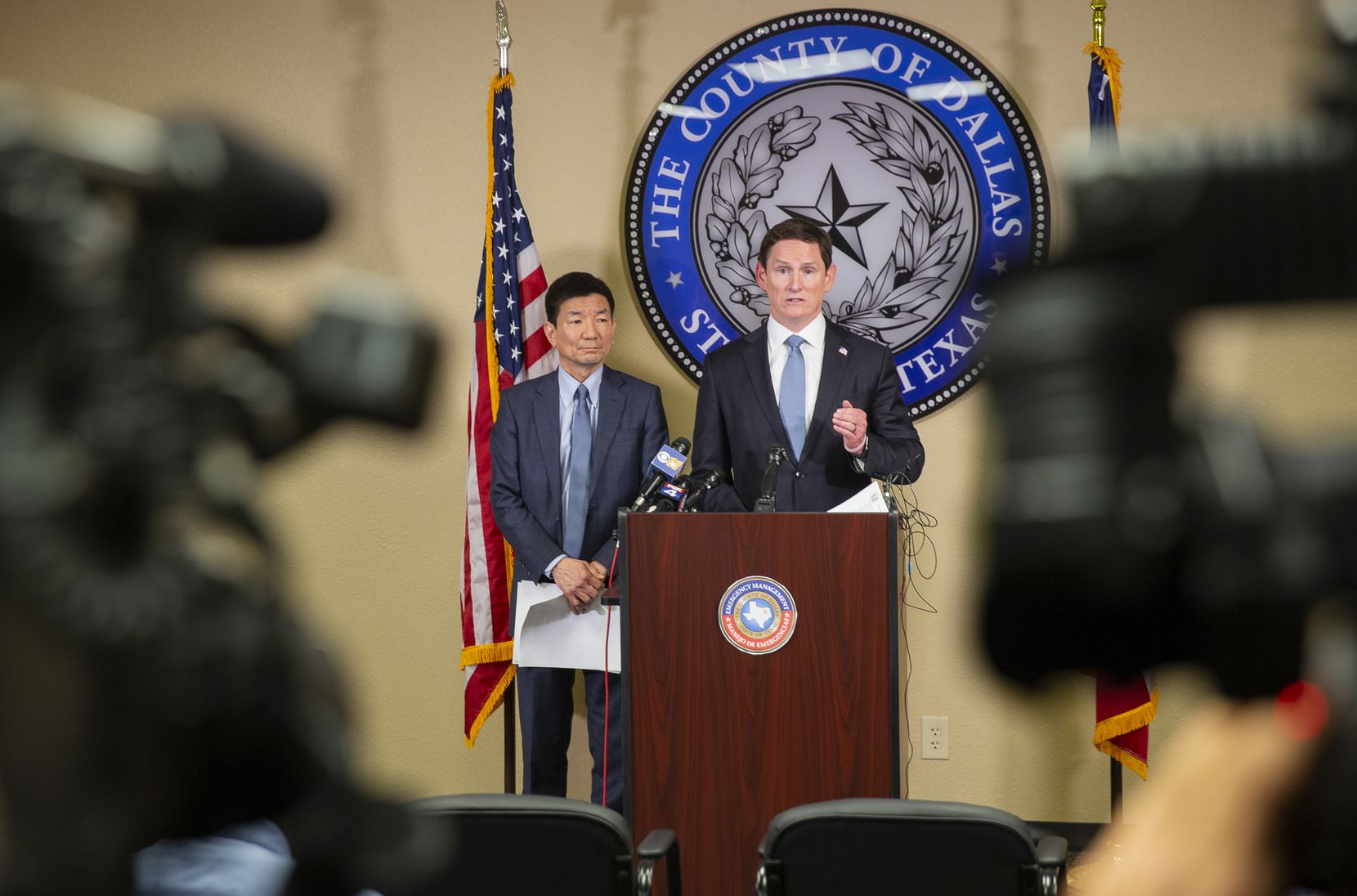 Dallas County Judge Clay Jenkins (right) and Dr. Philip Huang, director of Dallas County Health and Human Services, ordered bars and restaurants to shut down throughout the area to help stem the new coronavirus at a news conference on March 16, 2020, in Dallas.