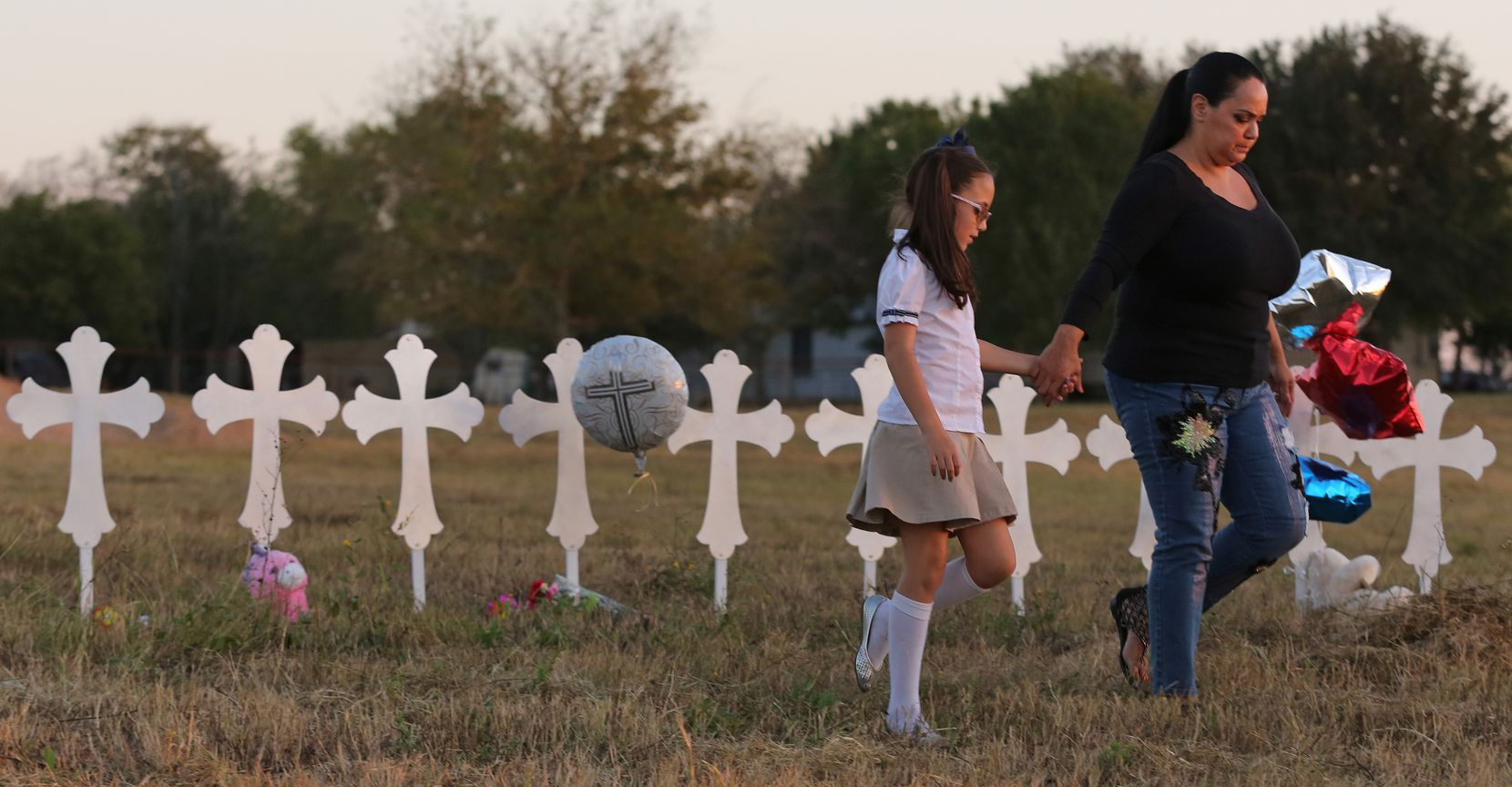 Eight-year-old Heather Cooper and her mother, Meredith Cooper, of San Antonio walk away after placing a remembrance at the 26 crosses placed in a field in Sutherland Springs to honor those who were killed in Sunday's mass shooting.
