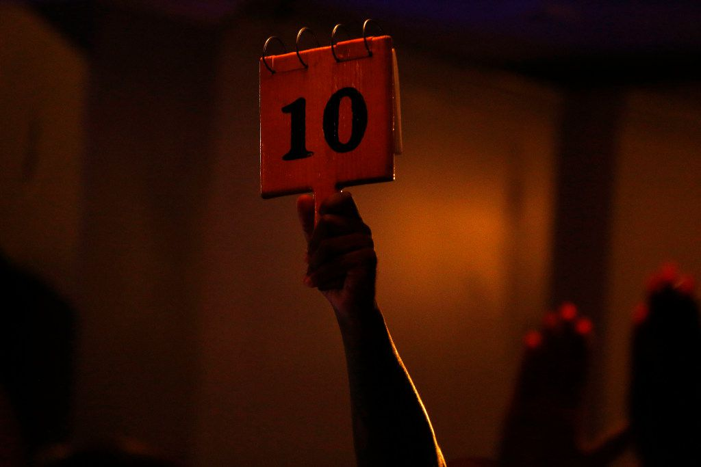 A judge gives a poet a perfect 10 score during a Dallas Poetry Slam open mic. Slam performances are scored based on a number of criteria, including delivery, writing and a set time limit.