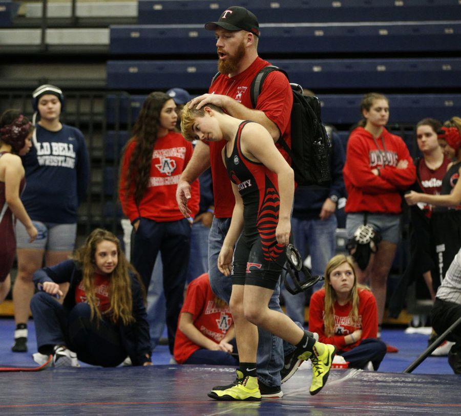 Euless Trinity High School wrestler Mack Beggs walked off the mat with coach Travis Clark after Mack's opponent forfeited the girls 110-pound Class 6A Region II match Saturday. (Nathan Hunsinger/Staff Photographer)