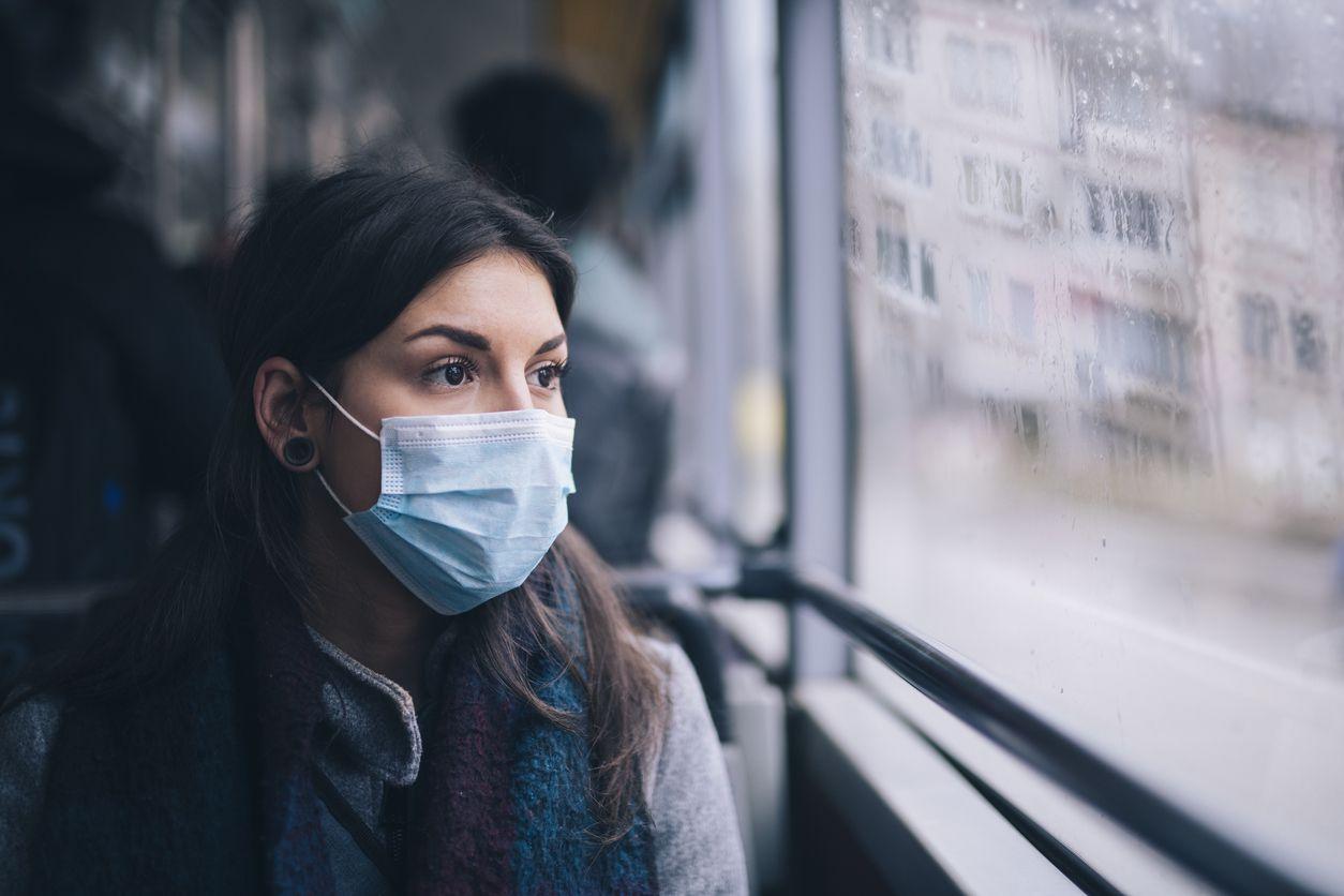 Una mujer porta un cubrebocas en un camión de transporte público.
