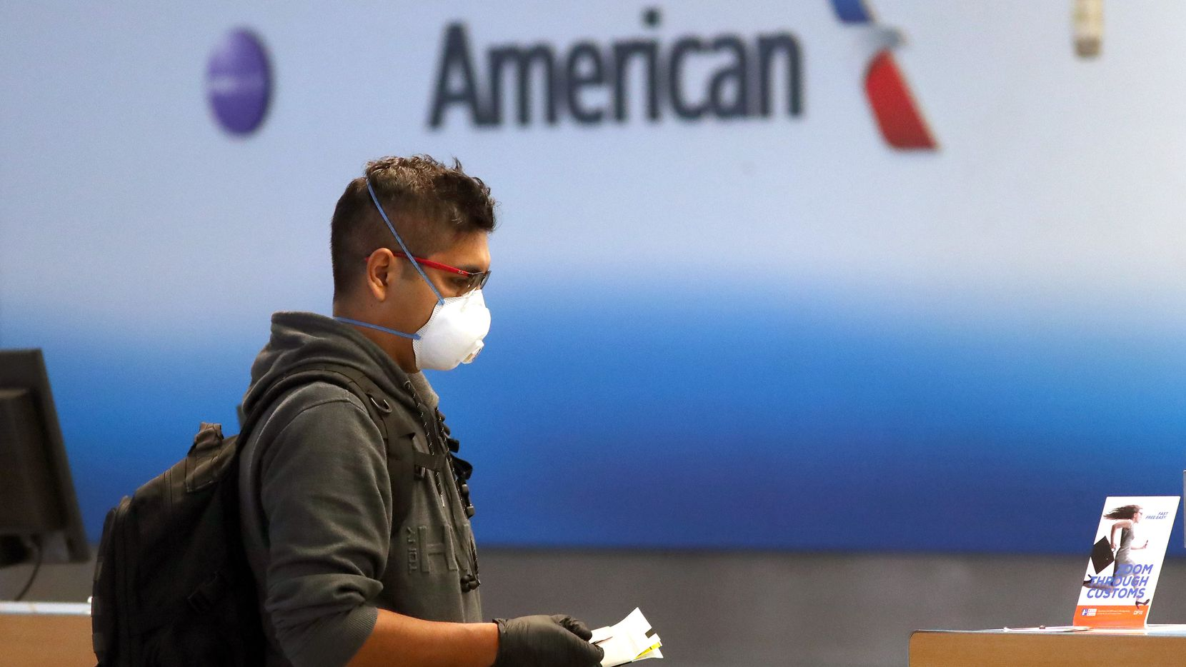 A passenger checked in for an American Airlines flight in Terminal D at DFW International Airport on March 13, 2020. American Airlines announced that it is cutting a third of its international flights amid a major slowdown due to the coronavirus outbreak.