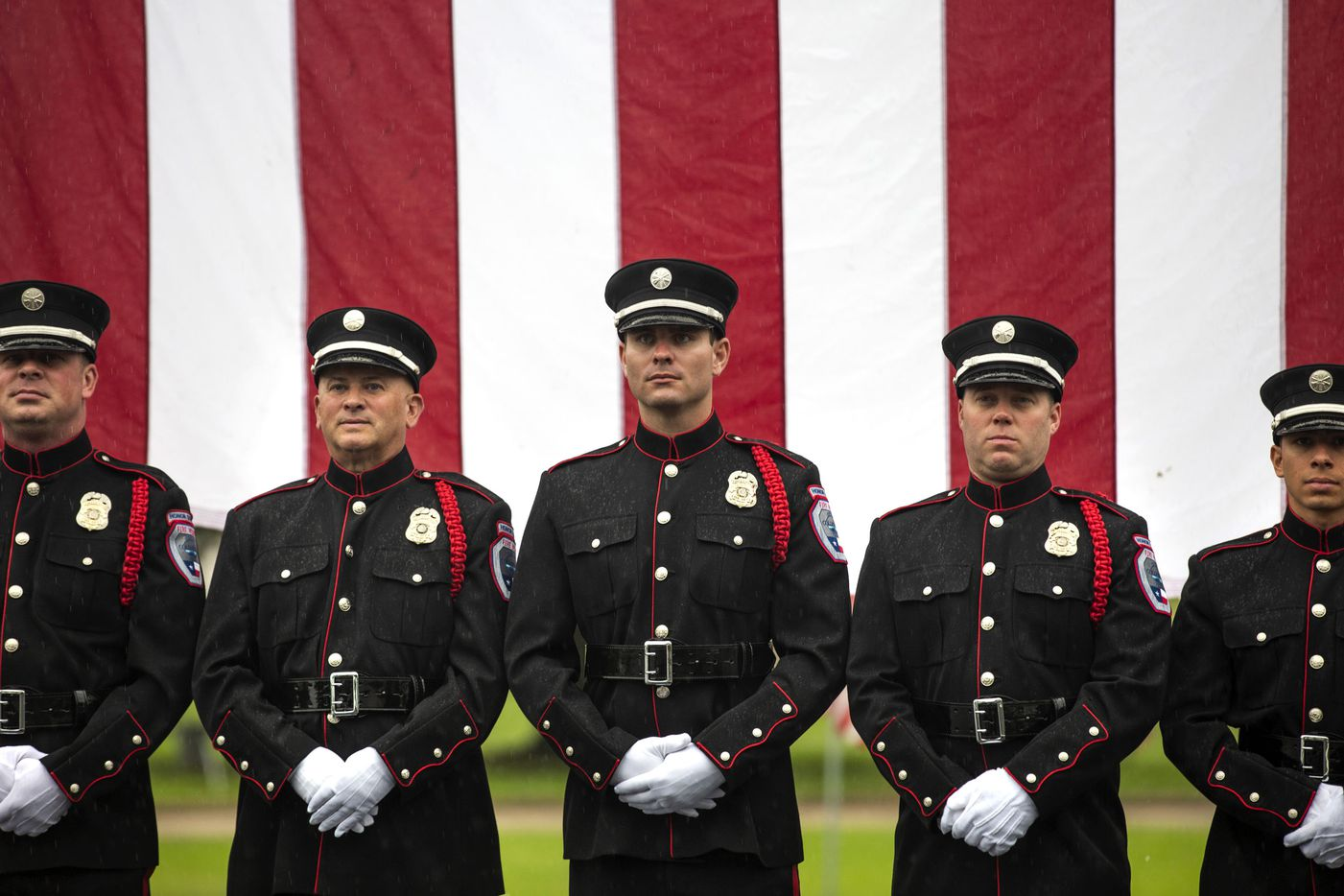From left, Matt Olson, William Savage, Jason Fisch, William Hutton and Martin Mendoza  of the Colleyville Fire Department Honor Guard stand beneath a large American flag for a photo following their participation in the the virtual Memorial Day Remembrance Ceremony at the Bluebonnet Hills Funeral Home in Colleyville, Texas, on Monday, May 25, 2020.