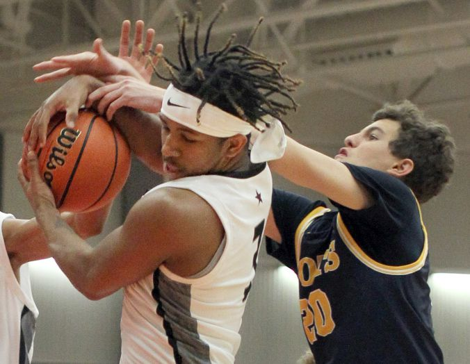 Coppell guard KJ Liggins (3) muscles down a rebound over Highland Park's Camp Wagner (20) during first half action. The two teams played their non district basketball game at Coppell High School in Coppell on December 29, 2020.