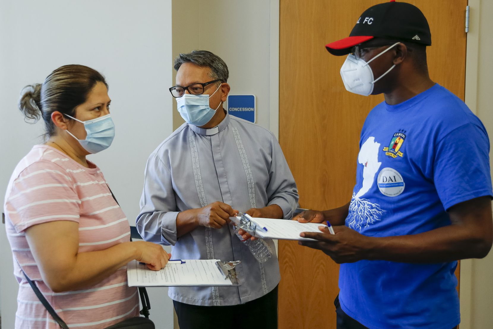 Maria Cruz of Dallas (left) receives help with paperwork from the Rev. Salvador Guzman (center) and Francis Basebang, leader with Dallas Area Interfaith, during a COVID-19 vaccination clinic at St. Pius X Catholic Church on Saturday, June 19, 2021, in Dallas.
