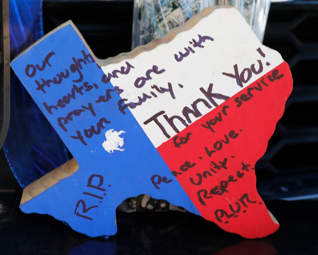 A wooden thank you note was placed on a police vehicle at Richardson police headquarters on Thursday. A Richardson police officer was fatally shot the night before at an apartment complex.