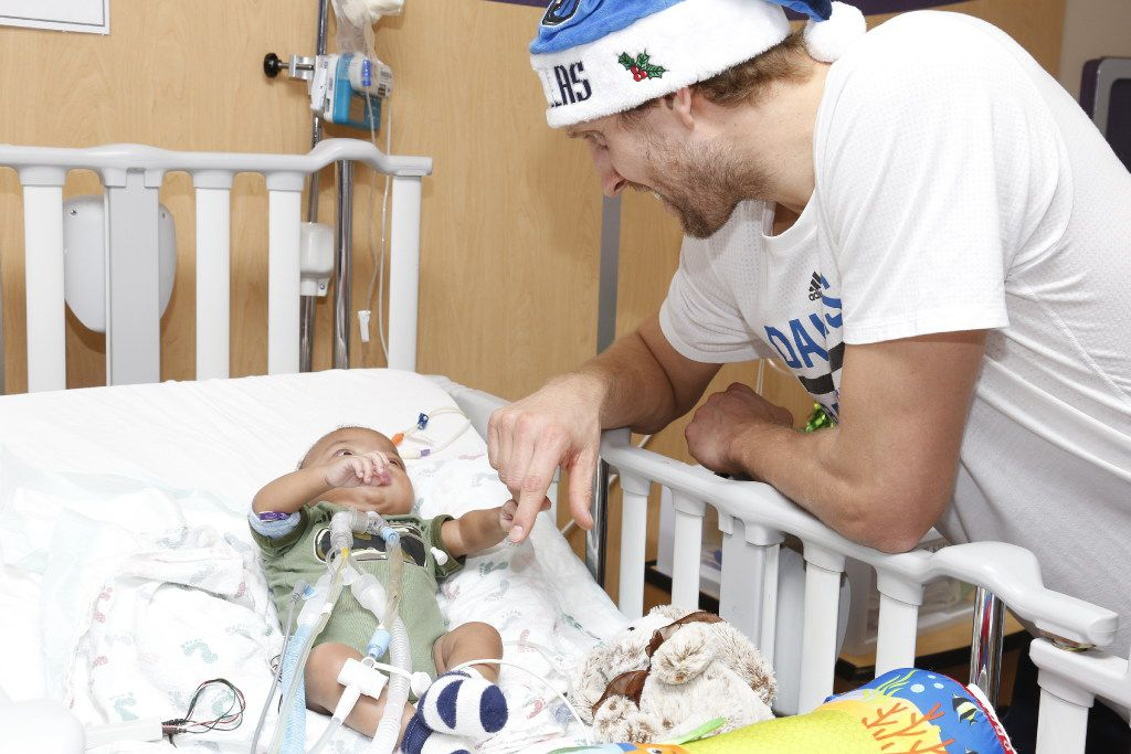 "Ryan, 8 months old, grabs Dirk Nowitzki's finger at Children's Medical Center. ""He's got a strong grip,"" Nowitzki said."