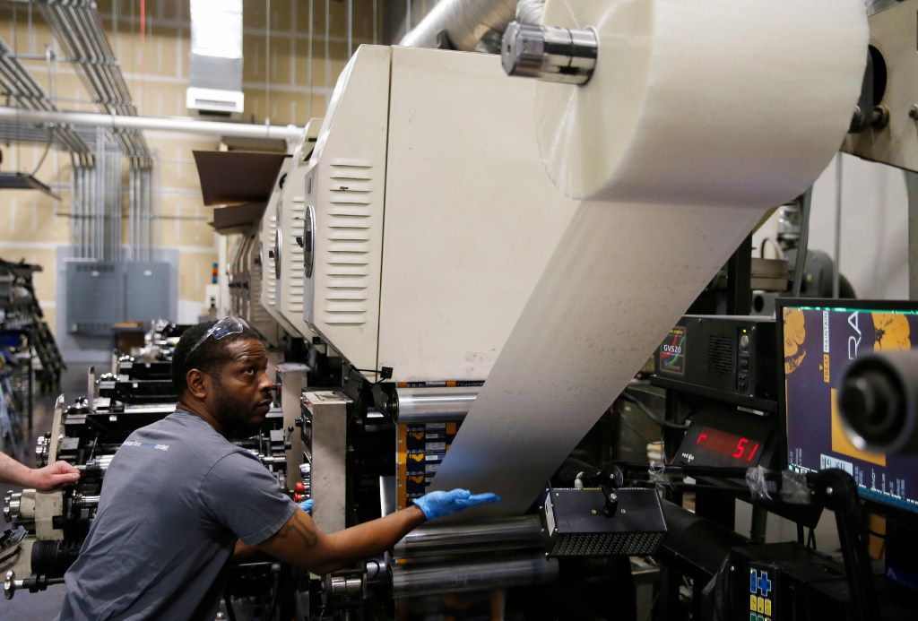 Marlon Booker works on feeding the press as he works on the flexographic press at Popular Ink in McKinney on Tuesday, February 14, 2017. Popular Ink specializes in printing flexible packaging materials. (Vernon Bryant/The Dallas Morning News)