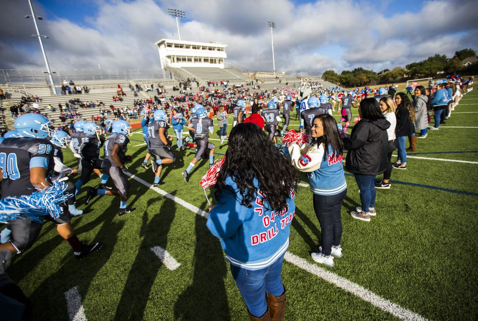 Thomas Jefferson High School football players run out onto the field for their homecoming game against Spruce High on Saturday.