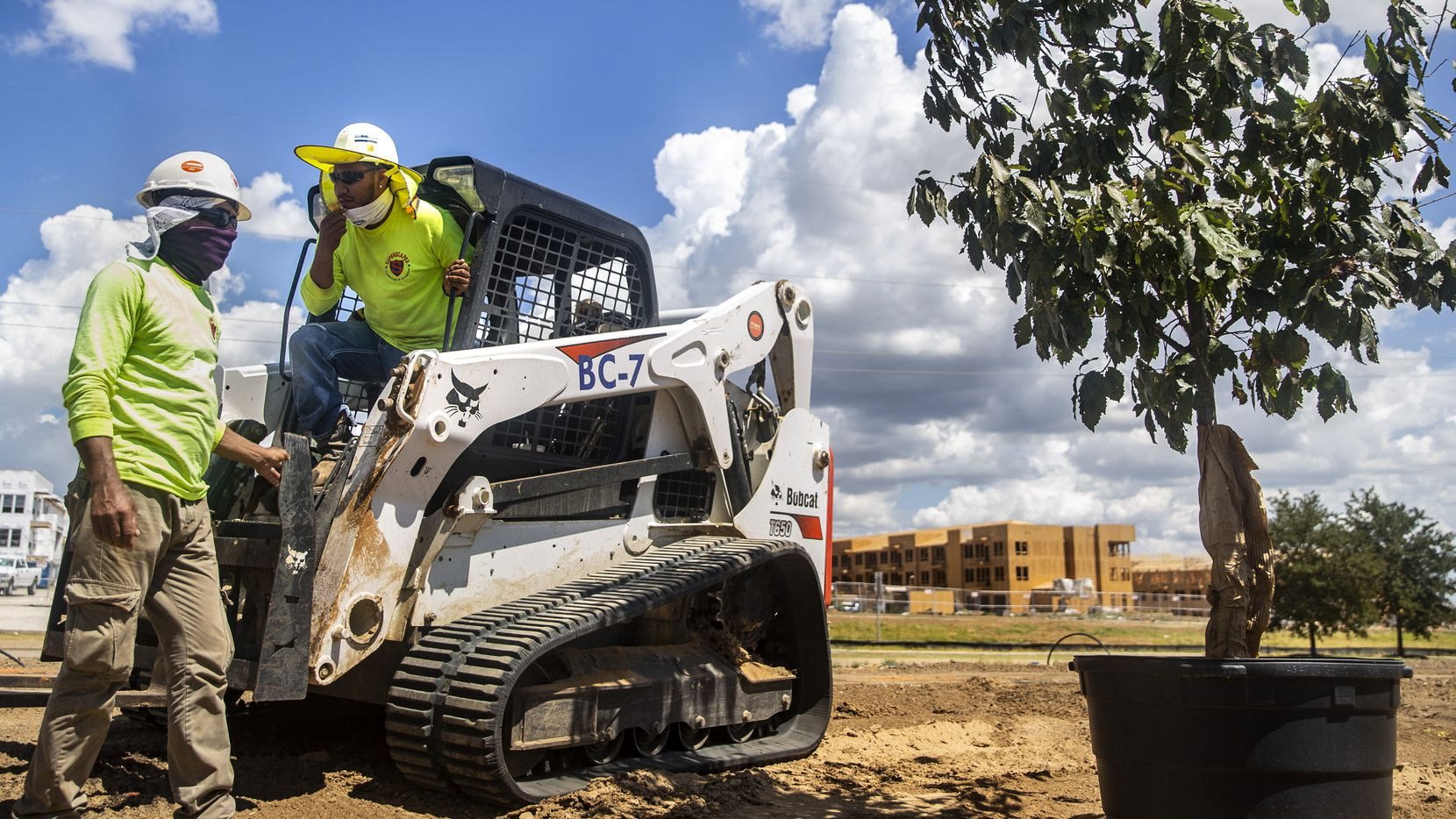 Superscapes landscaping foreman Martin Guerrero (right) works with landscaper Jesus Oliva at a job site at Lakeside Center in Flower Mound on Aug. 27.