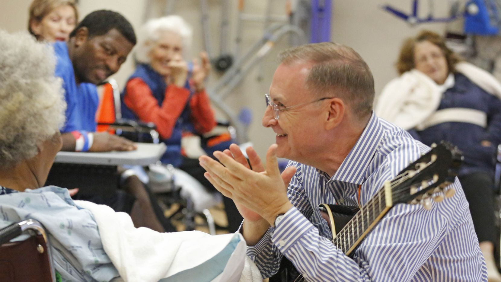 Michael Richardson, right, plays guitar and sings during a music therapy clinic at Texas Health Presbyterian Hospital Dallas, which holds the class for people with Parkinson's disease, traumatic brain injury and stroke.