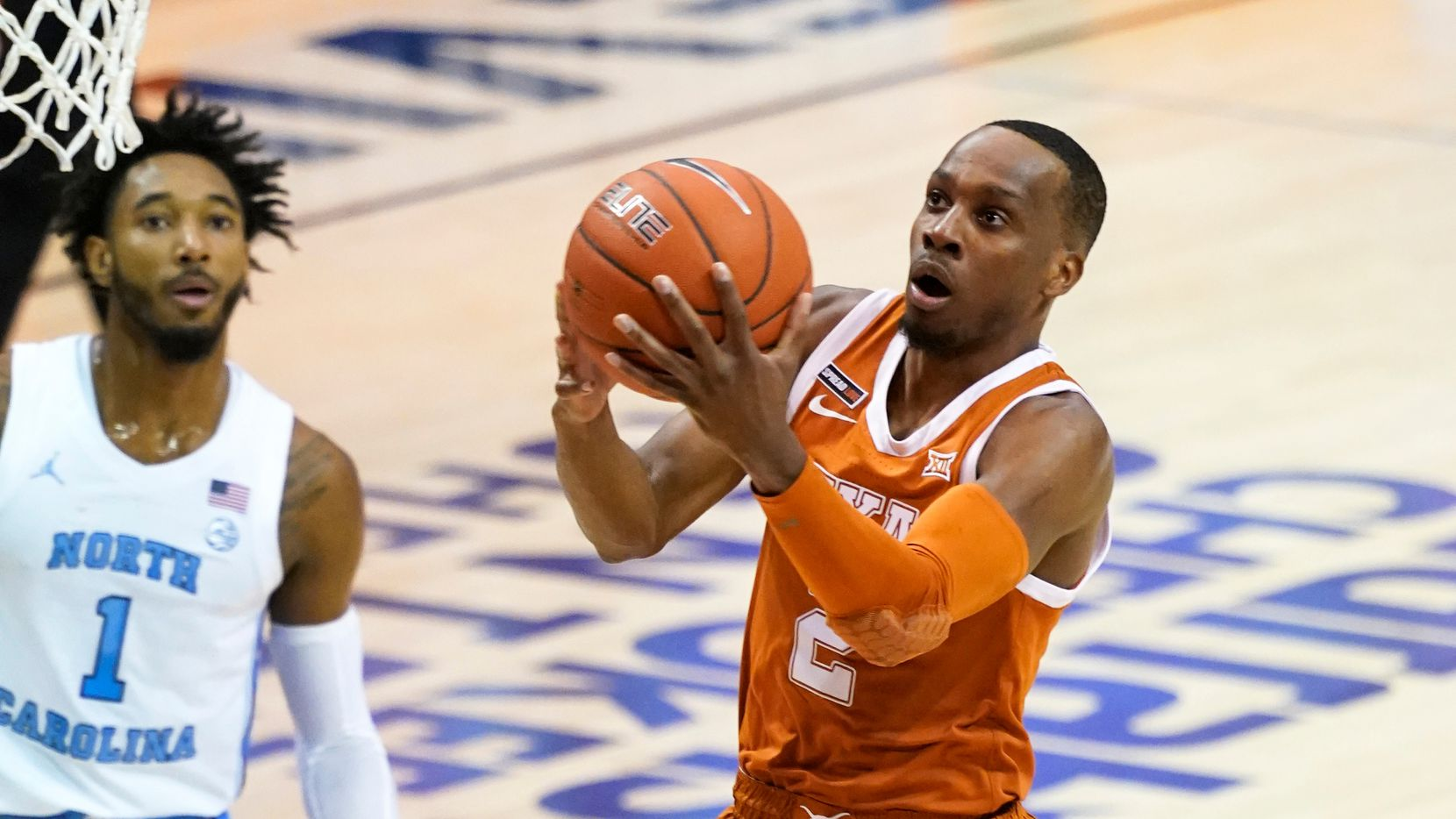 Texas guard Matt Coleman III (2) drives the ball to the basket past North Carolina guard R.J. Davis (4) and North Carolina guard Leaky Black (1) in the first half an NCAA college basketball game for the championship of the Maui Invitational, Wednesday, Dec. 2, 2020, in Asheville, N.C.