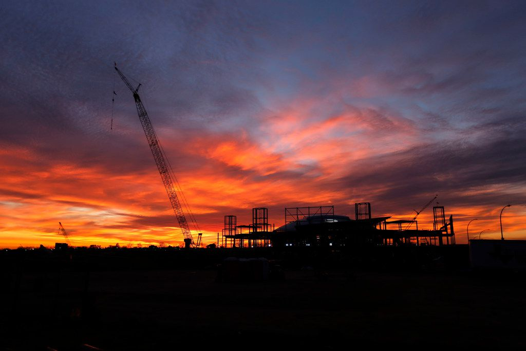 The sun sets behind AT&T Stadium and the Texas Live! construction site in Arlington.