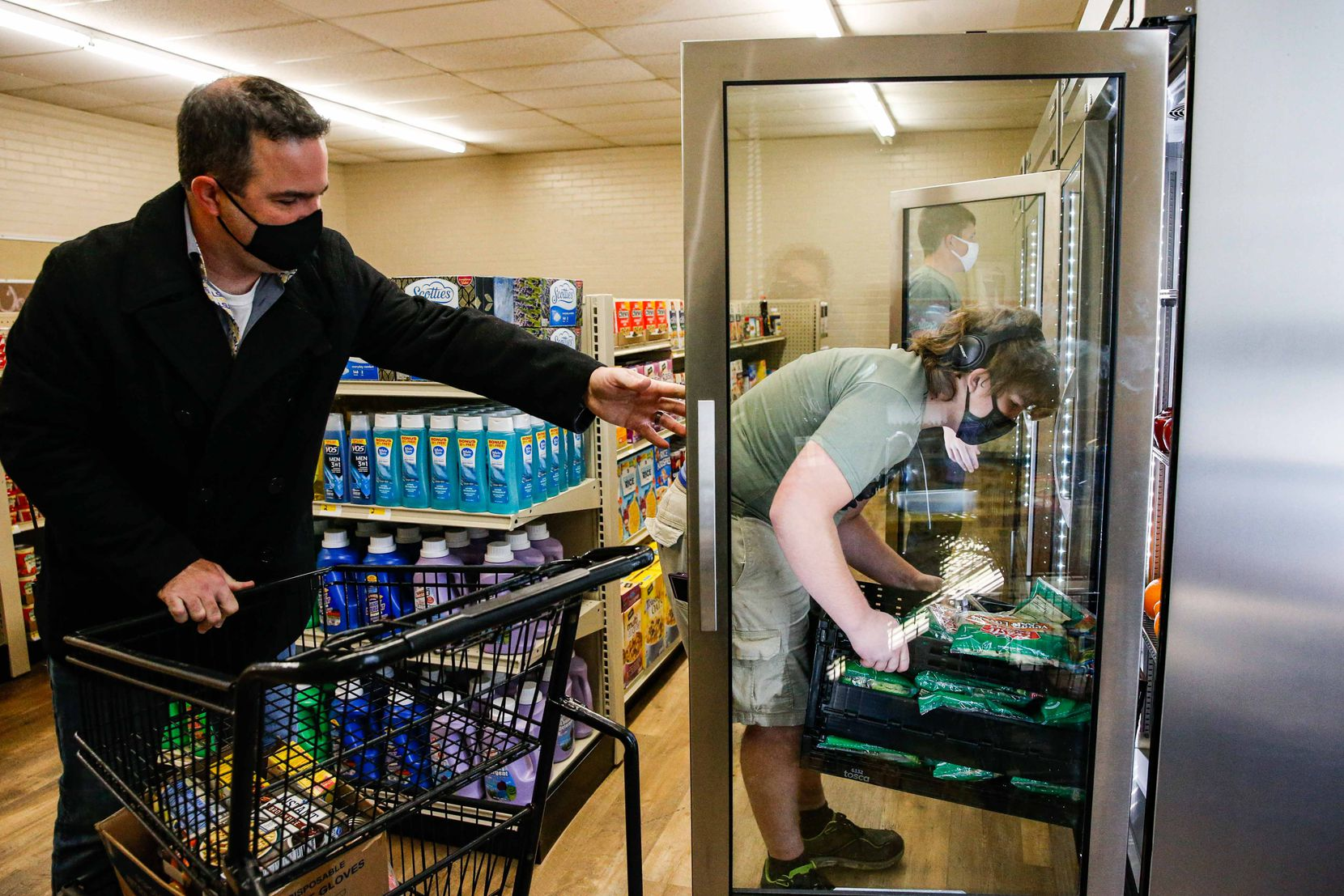 Linda Tutt High School principal Anthony Love helps Preston Westbrook stock a freezer at the school's grocery store.