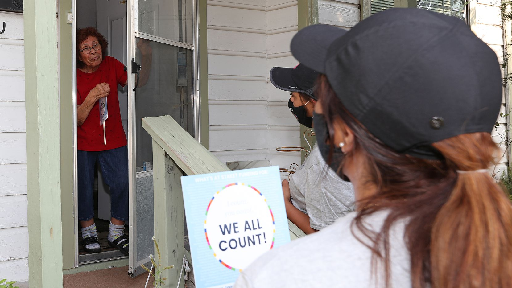 Emma Garza, 81, receives an invitation from volunteers with The Concilio to fill out the 2020 Census at her home near Bachman Lake.