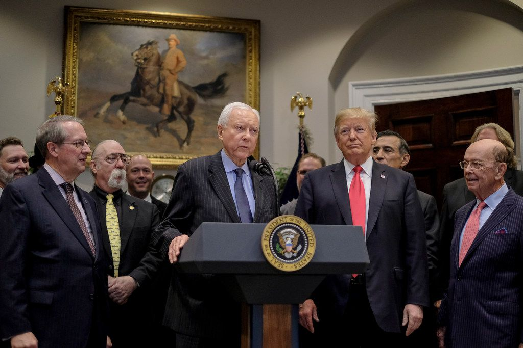 Sen. Orrin Hatch (R-Utah) speaks as President Donald Trump looks on during the signing of the Orrin G. Hatch-Bob Goodlatte Music Modernization Act in the Roosevelt Room of the White House on Oct. 11, 2018. From left: Rep. Bob Goodlatte (R-Va.), musician Jeff Baxter, Hatch, Trump, and Commerce Secretary Wilbur Ross.