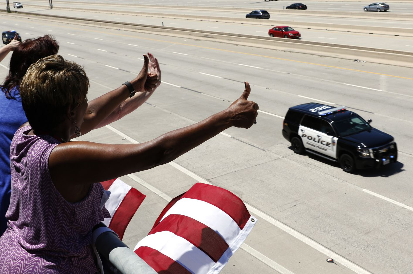 Sandra Forte and other employees from SBB Management Company wave and give thumbs up to passing police vehicles as they proceed east on Interstate 635 to Restland Funeral Home.
