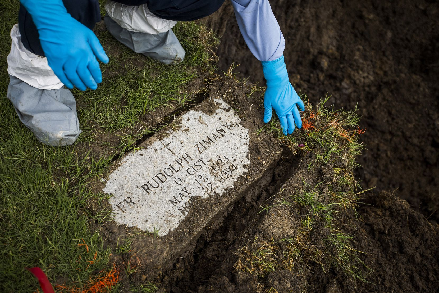 Calvary Hill Cemetery worker Andres Buenrostro removes the headstone of the Rev. Rudolph Zimanyi before the monk's remains were lifted from the grave he had occupied for nearly 23 years.