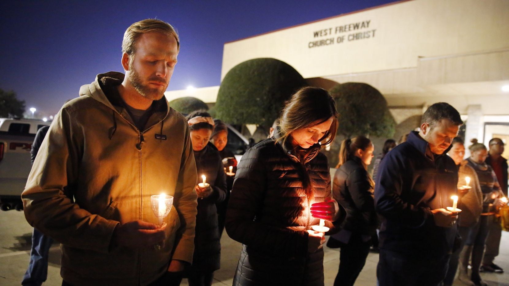 Church and community members, including Matt Pacholczyk (left) and his wife, Faith Pacholczyk, gathered outside the West Freeway Church of Christ in Fort Worth for a candlelight vigil Monday evening.
