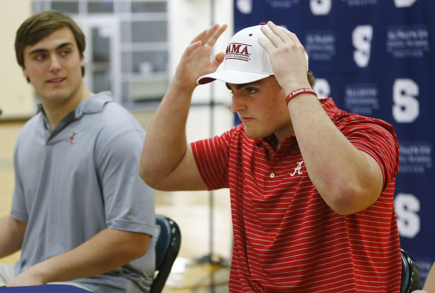 Fort Worth All Saints' Episcopal School James Brockermeyer adjusts his Alabama hat after signing a national letter of intent to play there. Joining him at Alabama is his twin brother Tommy Brockermeyer (left) in the schools gymnasium, Wednesday, December 16, 2020. (Tom Fox/The Dallas Morning News)