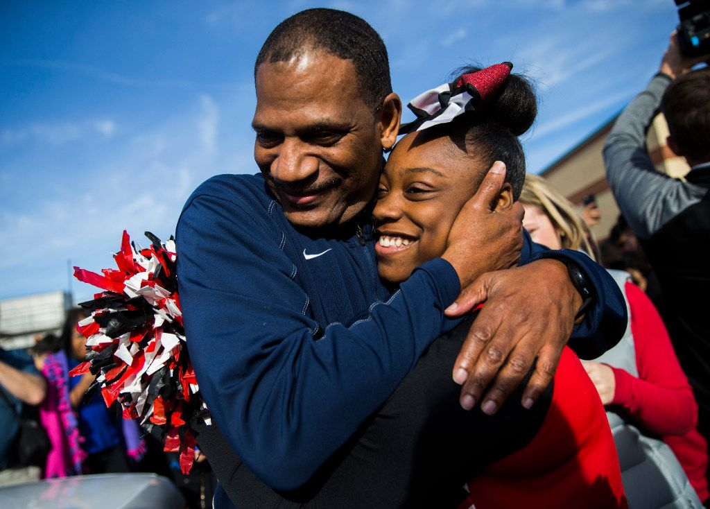 Kevin MaBone hugs cheerleader Aniya Sentell, 13, as he is surprised with a car during a presentation by students and teachers on Friday outside Wilkinson Middle School in Mesquite.