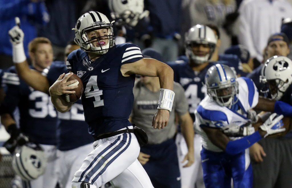 FILE - In this Sept. 27, 2013, file photo, BYU quarterback Taysom Hill (4) scores as he carries the ball against Middle Tennessee in the second quarter during an NCAA college football game, in Provo, Utah. BYU and their Heisman candidate, quarterback Hill is facing Connecticut Friday in East Hartford, in a nationally televised game. (AP Photo/Rick Bowmer, File) 09062014xSPORTS