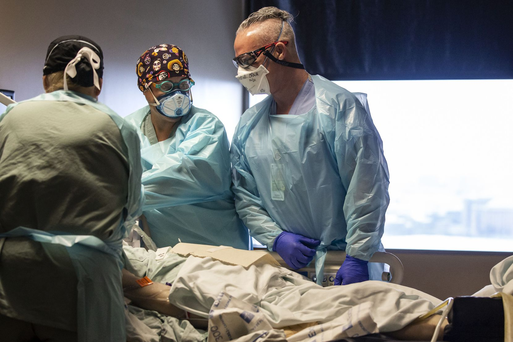 From left, respiratory therapists Shannon Harden and Raquel Martinez, and certified registered nurse anesthetist Brandon Mitchell change a breathing tube for a patient in the COVID-19 intensive care unit at Parkland on Monday.