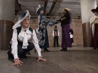 """Sadie Redmond as Arabella Matthews, far left, crouches during a rehearsal of Cry Havoc Theater Company's devised play, """"Committed: Mad Women of the Asylum,"""" in the basement of Southside on Lamar."""