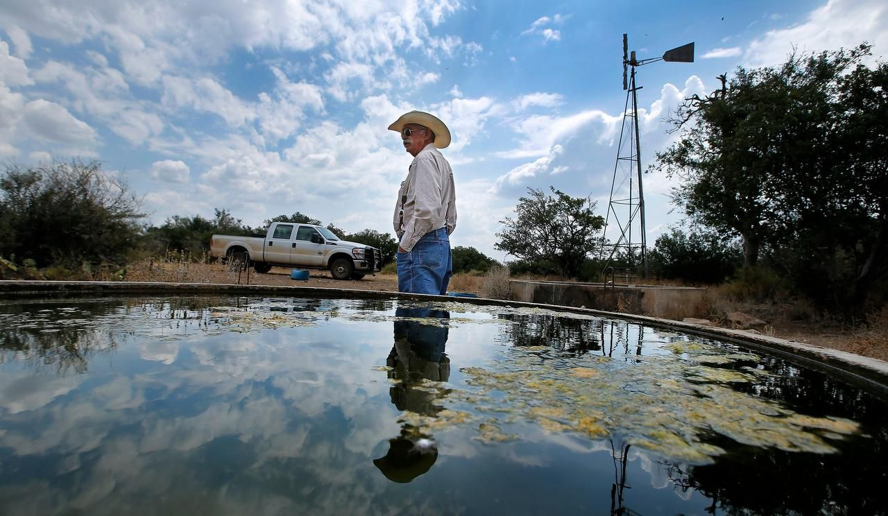Lifelong rancher Ron Crocker, who owns and runs CA Cattle Company outside of Mason, Texas, checks on his windmill driven freshwater stock pools. Crocker has a front door view of the Long Mountain range where proposed wind turbines are being planned.