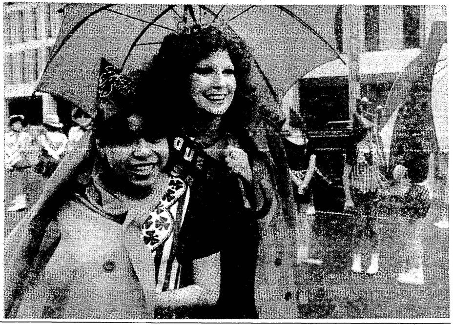 Image published in The Dallas Morning News on March 18, 1984. Original caption: At the downtown Dallas parade, the queen of the parade helped one of the Vikingettes keep warm and dry before the parade.