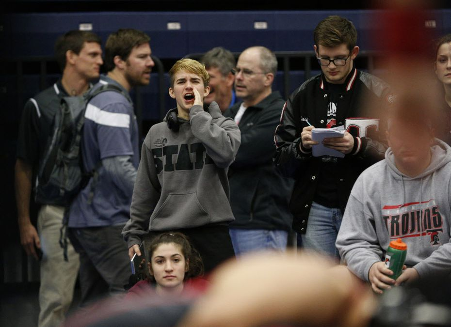 Euless Trinity's Mack Beggs (center left) cheers on his teammates during the Class 6A Region II wrestling meet at Allen High School.