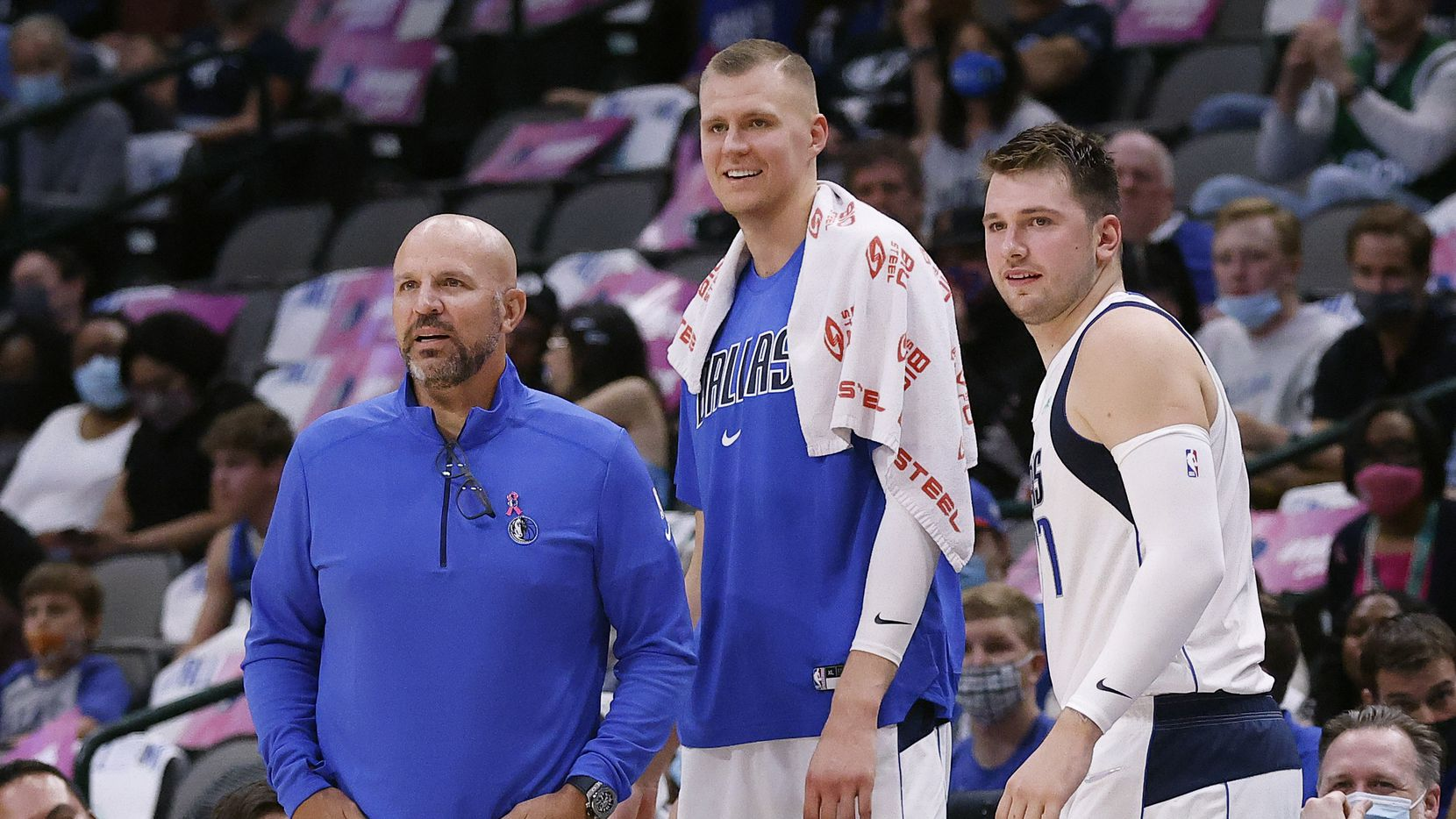 Dallas Mavericks head coach Jason Kidd, center Kristaps Porzingis (center) and guard Luka Doncic watch from the scorers table as the team competes against the Utah Jazz in the first half at the American Airlines Center in Dallas, Wednesday, October 6, 2021.