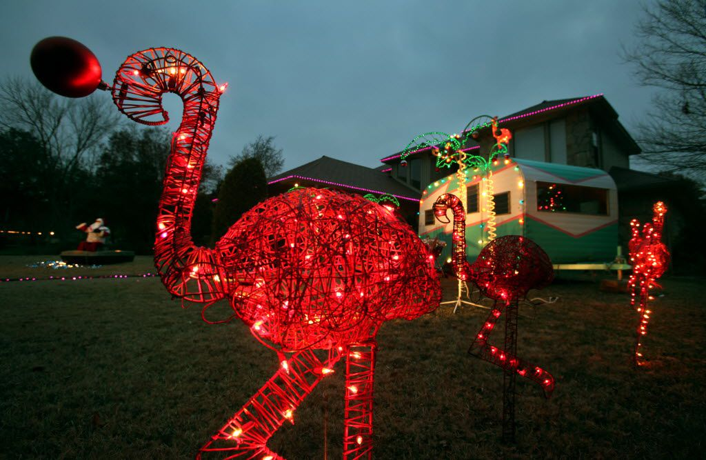 "In this file photo from a previous year's event, lighted pink flamingos and a travel trailer with a ""gone fishing"" sign were on display in Arlington's Interlochen neighborhood."
