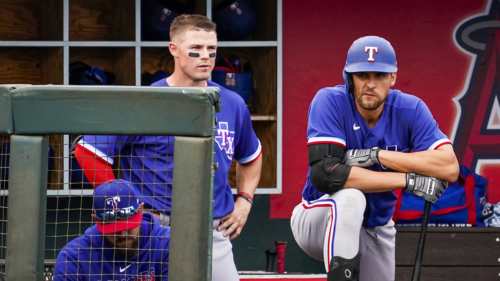 Texas Rangers infielder Greg Bird (right) and outfielder Scott Heineman watch from the dugout during the sixth inning of a spring training game against the Los Angeles Angels at Tempe Diablo Stadium on Friday, Feb. 28, 2020, in Tempe, Ariz.