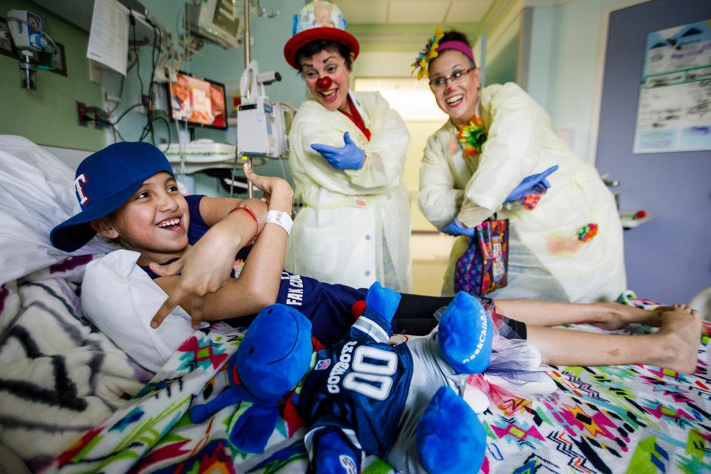"Therapeutic medical clowns Tiffany Riley, a.k.a. ""Dr. Slappy"" (center), and Marcie Brannon, a.k.a. ""Dr. Dainty,""  entertain patient Marissa Leal, 10, in her hospital room at Cook Children's Medical Center in Fort Worth."