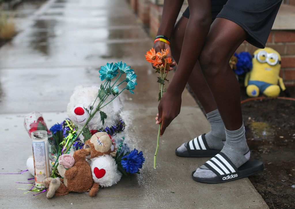 An attendee of a Sterlinshire Apartments community center daycare program lays a flower on a memorial near where 13-year-old Malik Tyler, of Dallas, was killed after being caught in the crossfire of a shootout near a Pleasant Grove gas station Tuesday evening on Wednesday, June 5, 2019 in Dallas. (Ryan Michalesko/The Dallas Morning News)