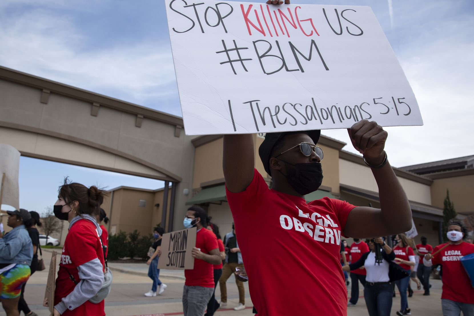 Zion Mayberry holds a sign as he participates in a march through the Allen Outlets on Sunday, March 21, 2021 demanding justice for Marvin Scott III, who died a week prior while in custody at the Collin County Jail on March 14, 2021. Marvin Scott III was arrested at the Allen Outlets for possession of less than two ounces of marijuana. (Shelby Tauber/Special Contributor)