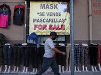 Una persona camina por enfrente de un negocio en el centro de El Paso donde se vende ropa y oferta también mascarillas protectoras al coronavirus.