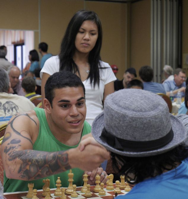 Nicholas Chrysanthou meets his opponent, Women's Grand Master Carla Heredia, with his fiancee, Sasha Hok, behind him at the start of the afternoon round of matches at the 79th Annual Southwest Chess Open in Irving.