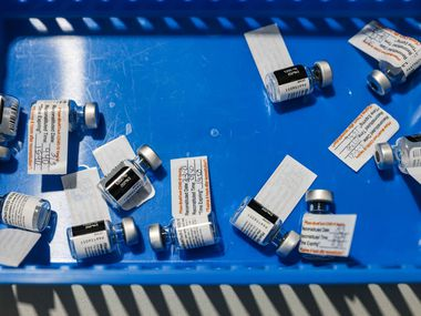 Used Pfizer-BioNTech COVID-19 vaccine vials rest in a blue tray at Ellis Davis Fieldhouse, a Parkland Hospital testing and vaccine location, in Dallas on Wednesday, March 3, 2021. (Lola Gomez/The Dallas Morning News)