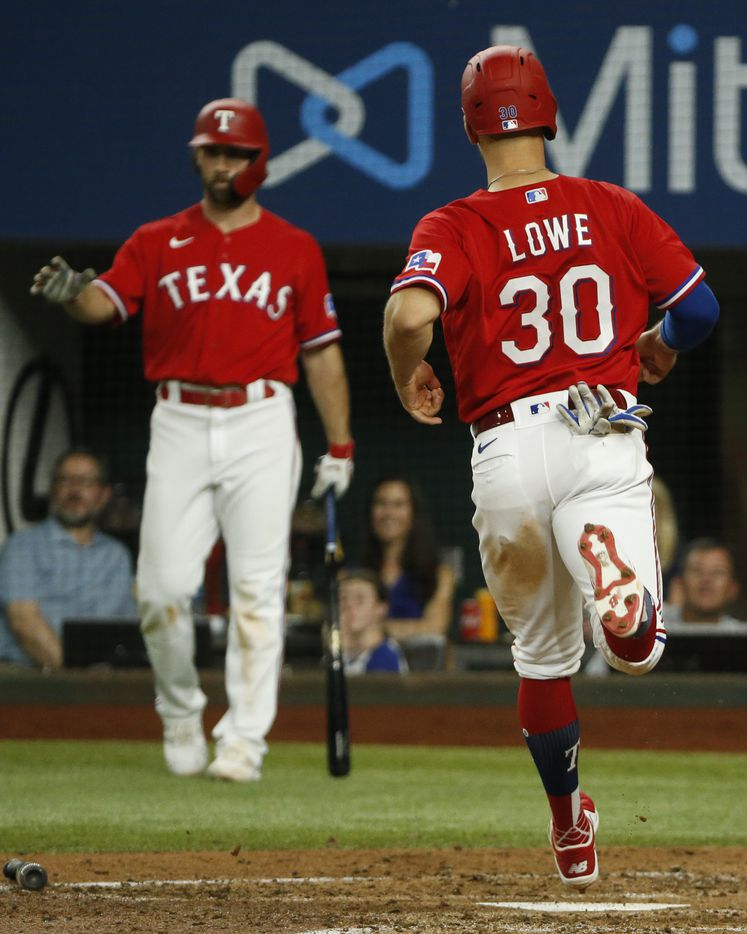 Texas Rangers first baseman Nate Lowe (30) touches home plate after an RBI double from Texas Rangers catcher Jonah Heim (28) during the sixth inning against the Kansas City Royals at Globe Life Field on Friday, June 25, 2021, in Arlington. (Elias Valverde II/The Dallas Morning News)