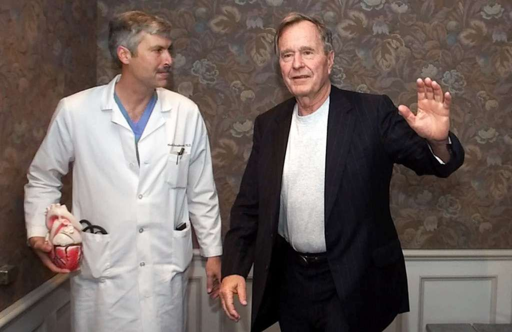 Former President George Bush, right, waves as he leaves with cardiologist Mark Hausknecht after a news conference at Methodist Hospital Feb. 25, 2000, in Houston.