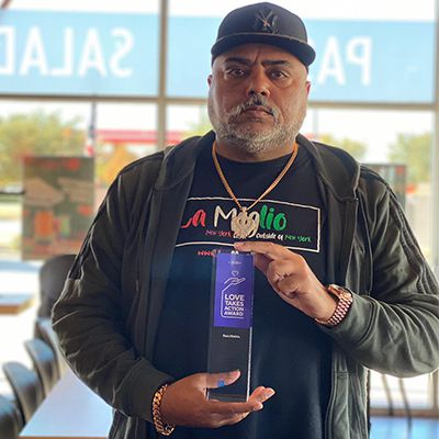 "Ram Mehta, owner of In-Fretta pizza in Plano, holds a ""Love Takes Action Award""  he received in 2020 from the New York Life Foundation for his charitable work."