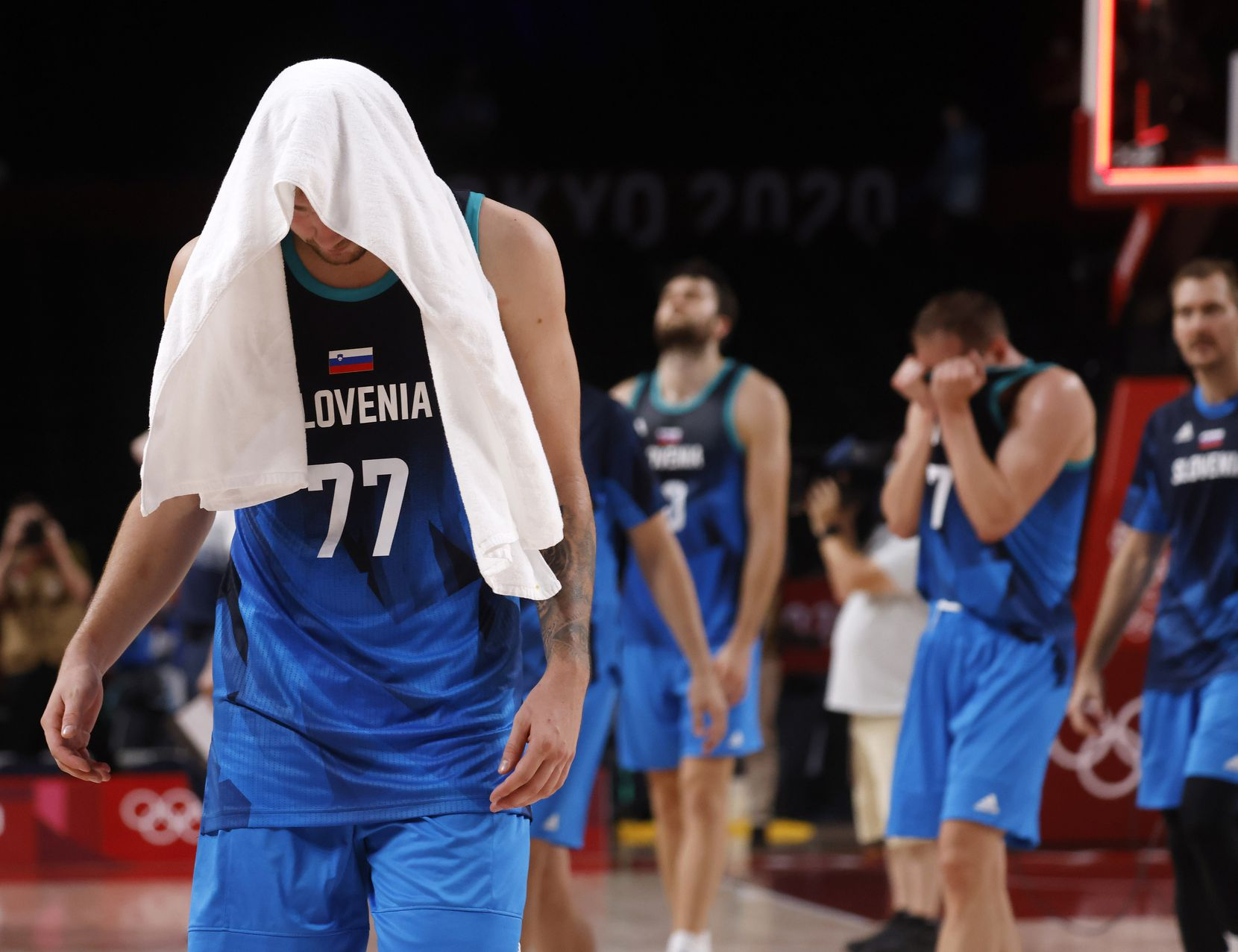 Slovenia's Luka Doncic (77) walks off the court dejected after losing to France 90-89 after a men's basketball semifinal at the postponed 2020 Tokyo Olympics at Saitama Super Arena, on Thursday, August 5, 2021, in Saitama, Japan. Slovenia's Klemenn Prepelic (7) is in tears after getting blocked by France's Nicolas Batum (5) on the final play. Slovenia will play in the bronze medal game. (Vernon Bryant/The Dallas Morning News)