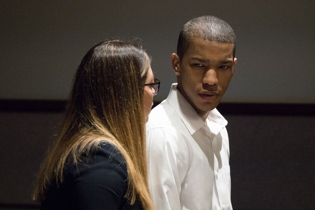 Defense attorney Camila Francino and defendant Eric Johnson talk Wednesday during a recess in his murder trial.