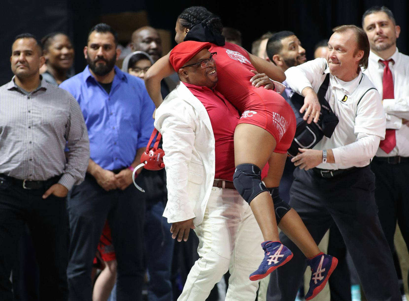 Kimball junior wrestler Destiny Miles embraces coach Devon Fortson after she won the UIL Class 5A girls 148-pound championship on Saturday, Feb. 23 at the Berry Center in Cypress, Texas. (Courtesy/Paul Brick)