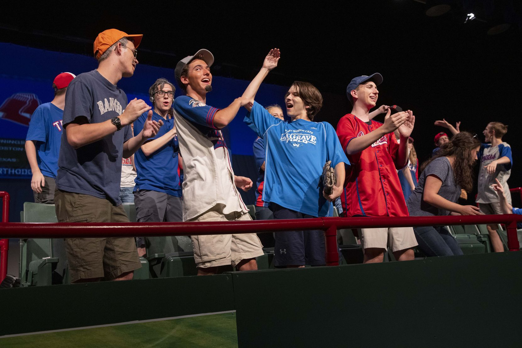 """Students reenact the home crowd during the 2011 Rangers versus Red Sox game during dress rehearsal the school's play """"One Strike Away"""" on Wednesday, Oct. 6, 2021, at Keller High School in Keller. (Juan Figueroa/The Dallas Morning News)"""