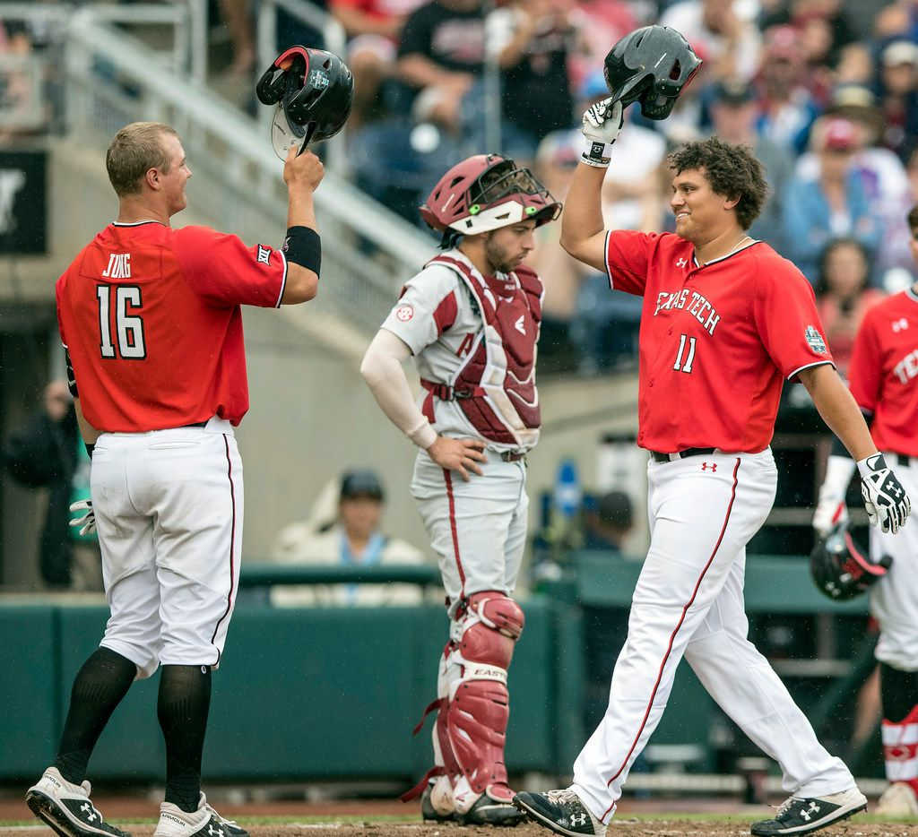 Texas Tech's Cameron Warren, right, celebrates his two-run home run with Josh Jung who also scored on the play in the fourth inning as Arkansas catcher Casey Opitz waits at home during an NCAA College World Series game in Omaha, Neb., Monday, June 17, 2019. (Brendan Sullivan/Omaha World-Herald via AP)